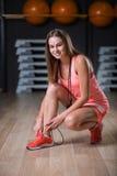Una hembra hermosa que lleva deportes rosados uniforma en un fondo del gimnasio Aptitud, actividad, y concepto del levantamiento  Imagen de archivo