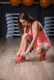 Una hembra hermosa que lleva deportes rosados uniforma en un fondo del gimnasio Aptitud, actividad, y concepto del levantamiento  Imágenes de archivo libres de regalías