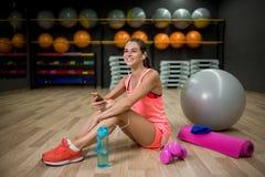 Una hembra hermosa y fuerte en ropa rosada en un fondo del gimnasio Concepto de la aptitud, de la dieta, deportivo y de la gente Foto de archivo libre de regalías
