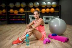 Una hembra hermosa y fuerte en ropa rosada en un fondo del gimnasio Concepto de la aptitud, de la dieta, deportivo y de la gente Fotografía de archivo