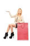 Una hembra joven atractiva que gesticula al lado de un bolso de compras Fotografía de archivo libre de regalías