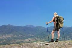 Una hembra joven con la mochila y polos el caminar en la montaña Fotografía de archivo libre de regalías