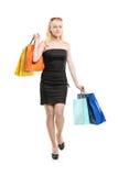 Una hembra joven sonriente que presenta con los bolsos de compras Imagen de archivo libre de regalías