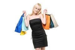 Una hembra joven sonriente que presenta con los bolsos de compras Imagenes de archivo