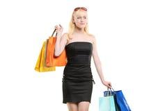 Una hembra joven sonriente que presenta con los bolsos de compras Imágenes de archivo libres de regalías