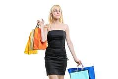 Una hembra joven sonriente que presenta con los bolsos de compras Fotografía de archivo