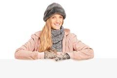 Una hembra joven sonriente que presenta detrás de un panel Imágenes de archivo libres de regalías