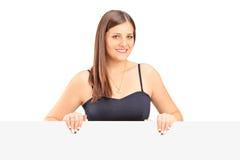 Una hembra joven sonriente que presenta detrás de un panel Imagen de archivo