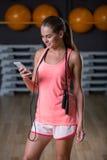Una hembra magnífica en los deportes rosados brillantes uniforma en un fondo del gimnasio Músculos del edificio, dieta y concepto Imagen de archivo libre de regalías