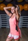 Una hembra magnífica en los deportes rosados brillantes uniforma en un fondo del gimnasio Músculos del edificio, dieta y concepto Fotos de archivo