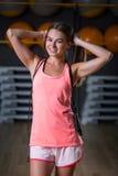 Una hembra magnífica en los deportes rosados brillantes uniforma en un fondo del gimnasio Músculos del edificio, dieta y concepto Fotografía de archivo libre de regalías