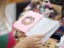Una hembra que sostiene un cuadernillo de apuntes de moda, original para las notas sobre un fondo borroso Una muchacha que elige  Imágenes de archivo libres de regalías