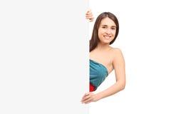 Una hembra sonriente que presenta en un panel en blanco Foto de archivo libre de regalías