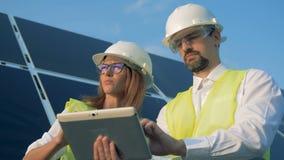 Una hembra y los ingenieros solares de sexo masculino está llevando a cabo una discusión almacen de metraje de vídeo
