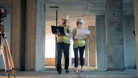 Una hembra y los trabajadores de una construcción del varón, constructores, constructores están caminando a lo largo del emplazam almacen de metraje de vídeo