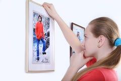 Una hermana más joven que mira cuidadosamente en el hermano de la foto aislado en la pared blanca Imagen de archivo libre de regalías