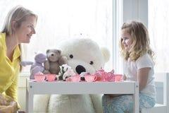 Una hija de la mamá y del niño que tiene una fiesta del té imagen de archivo libre de regalías