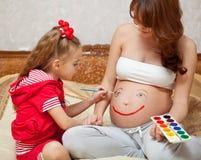Una hija es pintura en su vientre del `s de la madre Imagen de archivo libre de regalías