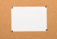 Una hoja blanca fijada en tablero del corcho Fotos de archivo libres de regalías
