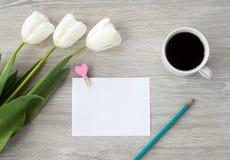 Una hoja de papel con una pluma roja, flores y una taza de mentiras del café en una tabla de madera blanca Deje una nota en la ta fotos de archivo libres de regalías