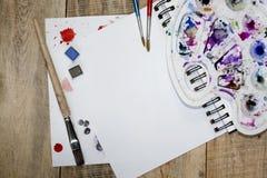 Una hoja de papel en blanco para el texto con los pétalos de la flor en un fondo de madera Ejemplo de una afición, de un dibujo y Fotografía de archivo