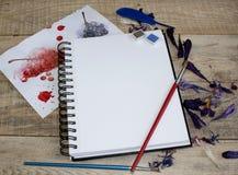 Una hoja de papel en blanco para el texto con los pétalos de la flor en un fondo de madera Ejemplo de una afición, de un dibujo y Fotografía de archivo libre de regalías