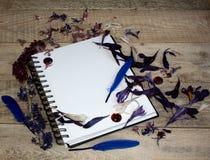 Una hoja de papel en blanco para el texto con los pétalos de la flor en un fondo de madera Ejemplo de una afición, de un dibujo y Imágenes de archivo libres de regalías