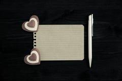 Una hoja de papel en blanco, pluma y dos corazones en un fondo de madera Foto de archivo