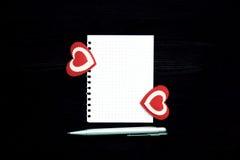 Una hoja de papel en blanco, pluma y dos corazones en un fondo de madera Imagenes de archivo