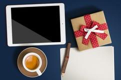 Una hoja de papel limpia, el café, la tableta y una pluma de madera ponen en b imagen de archivo