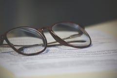 Una hoja de papel y un par de vidrios Foto de archivo