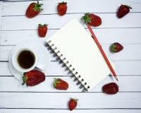 Una hoja en blanco del cuaderno en un fondo romántico rústico del fondo de madera con las fresas Una taza de café de la mañana Lu Imagen de archivo libre de regalías