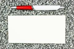 Una hoja y una pluma de la muestra-para arriba en la grava gris Foto de archivo