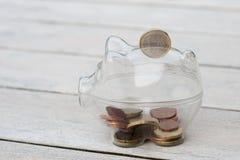 Una hucha, con las monedas cayendo en ranura. Imagen de archivo