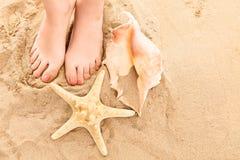 Una imagen arenosa de pies con una estrella de mar y un caracol Imagen de archivo
