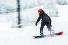 Una imagen borrosa muy rápida del tablero de la nieve del esquí del hombre Imagenes de archivo