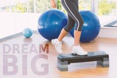 Una imagen compuesta de la sección baja de una mujer del ajuste que realiza ejercicio de los aeróbicos del paso Foto de archivo