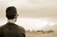 Hombre joven que mira hacia fuera sobre un nuevo futuro brillante Foto de archivo libre de regalías