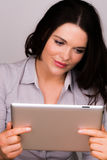 Hembra joven hermosa que usa un dispositivo de la tableta del ipad Fotos de archivo libres de regalías