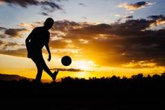 Una imagen de la acción de un grupo de niños que juegan al fútbol del fútbol para el ejercicio en zona rural de la comunidad bajo fotografía de archivo libre de regalías