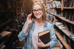 Una imagen de la muchacha atractiva que se coloca con un libro en su mano izquierda y que habla en el teléfono Ella está mirando  Imágenes de archivo libres de regalías