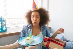 Una imagen de la muchacha del cumpleaños que explota la vela y que consigue un presente de sus amigos Imagenes de archivo