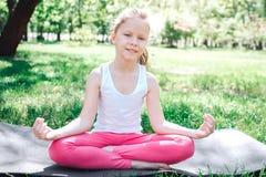 Una imagen de la muchacha del noce istting en la actitud del loto exterior y que mira en cámara Ella está sonriendo Yoga y concep Imagen de archivo libre de regalías