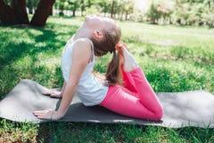 Una imagen de la muchacha flexible que alcanza su cabeza con el extremo de sus piernas Sh está haciendo algunos ejercicios afuera Fotos de archivo libres de regalías