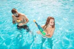Una imagen de la muchacha que ataca del individuo en piscina Él está tirando del arma de agua La muchacha está intentando defende imagen de archivo