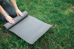 Una imagen de la mujer que rueda encima de carimate en hierba verde Yoga y concepto de Pilates Foto de archivo libre de regalías