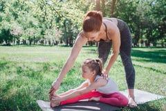 Una imagen de la mujer que se coloca sobre su hija y que le enseña a estirar La pequeña muchacha reacing su pie con sus manos Imagen de archivo libre de regalías