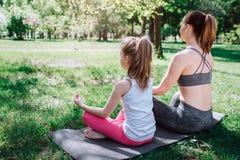 Una imagen de la parte posterior donde la mujer joven y la pequeña muchacha se están sentando en carimate en actitud del loto Se  Foto de archivo