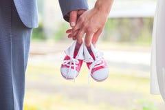 Una imagen de los adultos que sostienen pares del bebé de zapatillas de deporte en rojo Embarazo y expectativa Imágenes de archivo libres de regalías