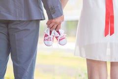Una imagen de los adultos que sostienen pares del bebé de zapatillas de deporte en rojo Embarazo y expectativa Fotos de archivo